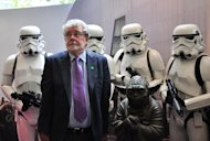 George Lucas poses with Stormtroopers and Yoda at the opening of Lucasfilms' new animation production facility, the Sandcrawler in Singapore on January 16, 2014