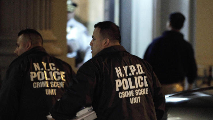 Crime scene unit officers enter the luxury Manhattan apartment building where police say a nanny stabbed two small children to death in a bathtub and then stabbed herself in New York, Thursday, Oct. 25, 2012. Police say the children's mother found the scene after returning home with another child. (AP Photo/Kathy Willens)