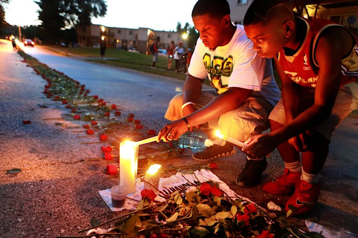 Theo Murphy, left, and his brother Jordan Marshall, 11, light candles at a memorial where unarmed Michael Brown was fatally shot by Ferguson Police Of...
