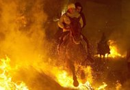 A horsewoman jumps over a bonfire at the Saint Anthony festival in Spain's San Bartolome de Pinares on Wednesday. About 100 Spanish horse riders jumped burning logs, flames leaping into the night, in a controversial, centuries-old rite celebrated every year in the village of San Bartolome de Pinares