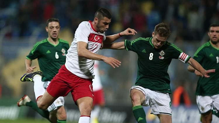 Turkey's Burak Yilmaz, left, and Steven Davis of Northern Ireland clash during their friendly soccer match in Adana, Turkey,  Friday, Nov. 15, 2013. (AP Photo)
