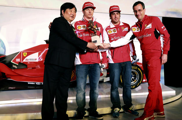 Tan Xuguang, left, chairman of Weichai Power, shakes hands with Stefano Domenicali, right, Ferrari team principal, as drivers Kimi Raikkonen, second left, and Fernando Alonso, second right, look on du