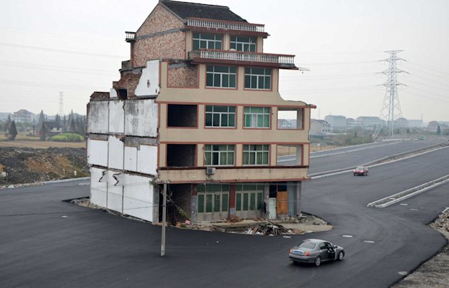 The house sits in the middle of the road as cars pass by