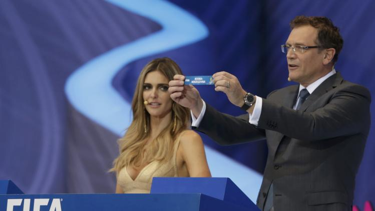 "Valcke holds up the slip showing ""Bosnia-Herzegovina"" during the draw for the 2014 World Cup in Sao Joao da Mata"