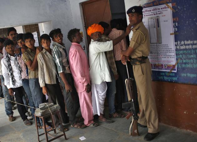 Men wait in a queue to cast their vote vote as a policeman stands guard at a polling station in Ajmer district in the desert Indian state of Rajasthan