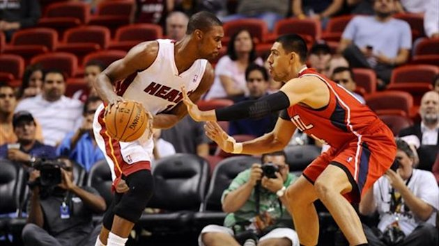 Miami Heat center Chris Bosh (1) is pressured by Atlanta Hawks power forward Gustavo Ayon (Reuters)