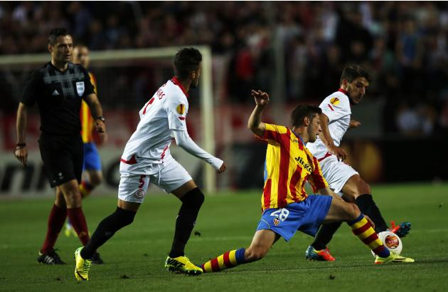 Sevilla's Diogo Figueiras and Valencia's Fede Cartabia battle for the ball during their soccer match in Seville