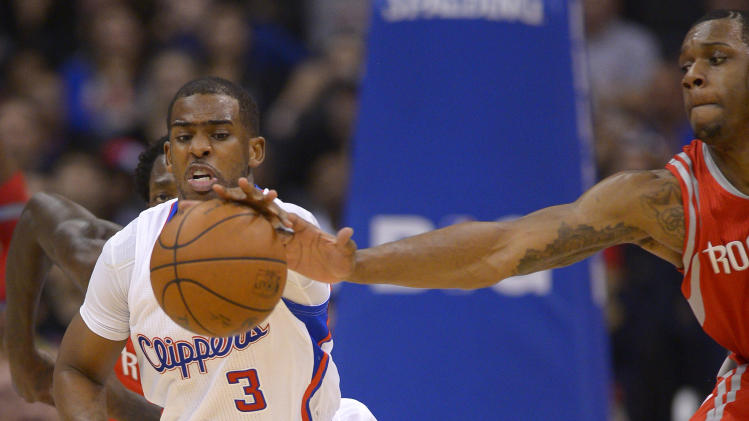 Los Angeles Clippers guard Chris Paul, left, reaches for a loose ball along with Houston Rockets forward Terrence Jones during the first half of an NBA basketball game, Wednesday, Feb. 26, 2014, in Los Angeles. (AP Photo/Mark J. Terrill)