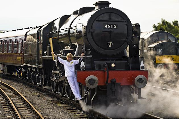 This image made available by LOCOG showsTorchbearer 004 Josephine Loughran carrying the Olympic Flame on the Scots Guardsman steam locomotive as they make the journey from York to Thirsk in England on