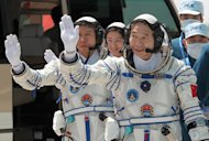 China's Shenzhou 9 crew, from right, Jing Haipeng, Liu Yang and Liu Wang, wearing their mission's emblem during training.