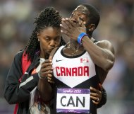 Canada's Justyn Warner is comforted after the team was disqualified from third place in the men's 4x100-meter relay, for running outside its lane, during Summer Olympics in London, Saturday, Aug. 11, 2012. (AP Photo/The Canadian Press, Ryan Remiorz)