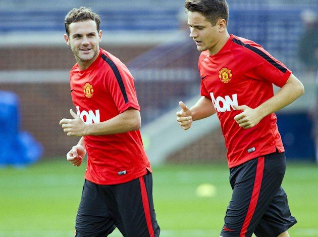 Manchester United midfielders Juan Mata, left, and Ander Herrera jog during a training session, Friday, Aug. 1, 2014, at Michigan Stadium in Ann Arbor, Mich. Real Madrid will face Manchester United in a Guinness International Champions Cup match Saturday at this college football stadium. (AP Photo/Tony Ding)