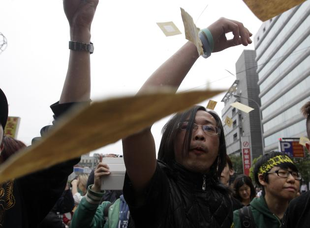 Anti-nuclear activists throw joss paper, also known as ghost money, during a protest in Taipei