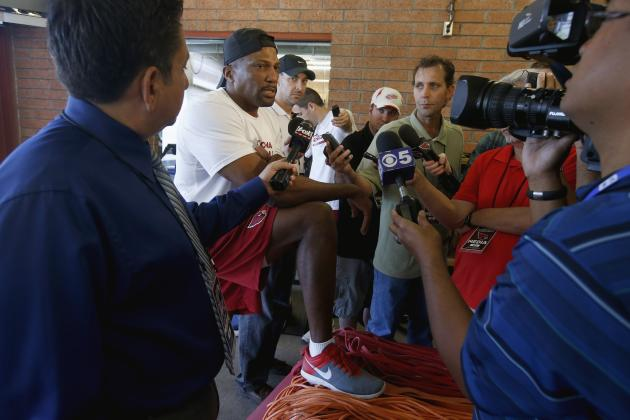 Former Olympic champion and the Arizona Cardinals' new assistant strength and conditioning coach, Roger Kingdom, second from left, talks with reporters after working out with Cardinals players dur