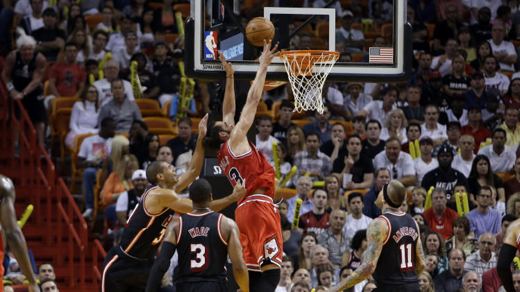 Chicago Bulls' Joakim Noah (13) shoots over Miami Heat's Shane Battier, left, Dwyane Wade (3), and Chris Andersen (11) during the first half of an NBA basketball game, Sunday, Feb. 23, 2014, in Miami. (AP Photo/Lynne Sladky)