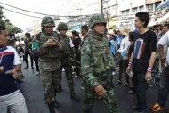 Thai military medics walk near the scene following an explosion at an anti-government protest camp at the Victory monument in central Bangkok January 19, 2014. REUTERS/Chaiwat Subprasom