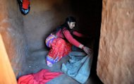 "Nepalese villager Chandrakal Nepali prepares her bedding inside a ""chhaupadi house"" in the village of Achham, some 800 km west of Kathmandu. Under the practice, women are prohibited from participating in normal family activities during menstruation and after childbirth"