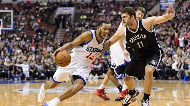 Philadelphia 76ers guard Evan Turner (12) is defended by Brooklyn Nets center Brook Lopez (11) during the fourth quarter at the Wells Fargo Center (Reuters)