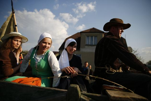 People dressed in historic costumes take part in a farewell celebration for a group of pilgrims from the knights brotherhood in Bratian near Brodnica