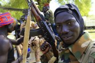 A South Sudan army soldier holds his weapon in Bor, 180 km (108 miles) northwest from capital Juba December 25, 2013. REUTERS/James Akena