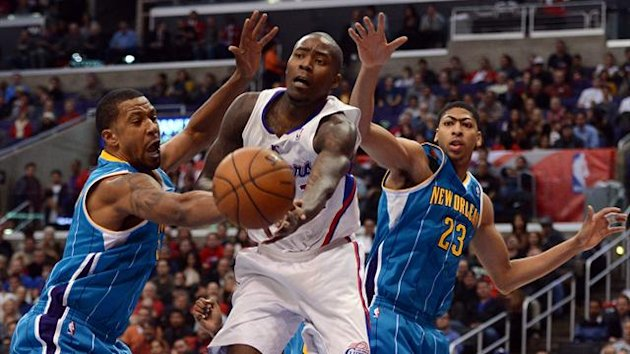Jamal Crawford #11 of the Los Angeles Clippers makes a pass in front of Dominic McGuire #5 and Anthony Davis #23 of the New Orleans Hornets during a 93-77 Clipper victory