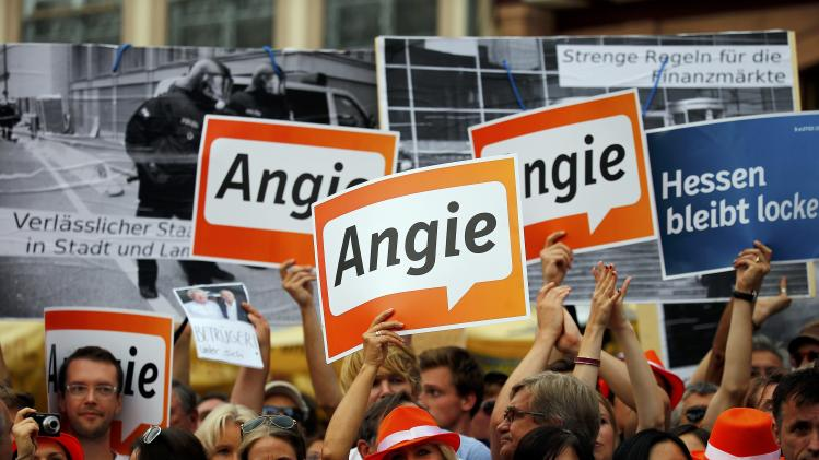 Supporters of German Chancellor and CDU leader Merkel hold up Angie posters to block the placards of protestors during an election campaign rally at Roemerberg square in Frankfurt