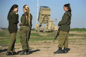 Israeli soldiers stand in front of the launcher of an Iron Dome missile interceptor battery deployed in Ashkelon