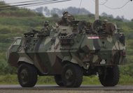 Malaysian soldiers drive towards the area where the stand-off with Sulu gunmen is ongoing, in Tanduo village on March 4, 2013. Malaysia Tuesday launched an attack with jet fighters and soldiers on up to 300 Filipino invaders in a bid to end a bloody three-week standoff in which 27 people had already been reported killed, including eight policemen