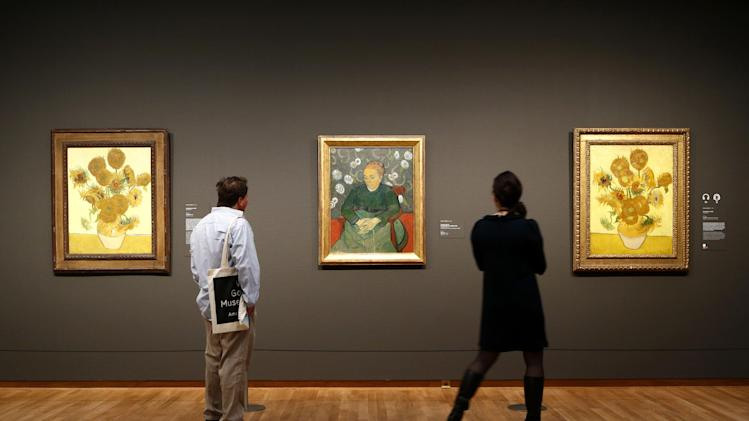 "Visitors look at paintings by Van Gogh, ""Sunflowers"" and ""La Berceuse (Woman Rocking a Cradle); Augustine Roulin"" at Van Gogh museum in Amsterdam, Netherlands, Wednesday, May 1, 2013. The Van Gogh Museum has reopened its doors to the public after a seven-month renovation, kicking off with ""Vincent At Work,"" an exhibition that shows Van Gogh's working methods, right down to the paints, brushes and other tools he used. (AP Photo/Vincent Jannink)"