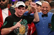 Canelo Alvarez (L) celebrates after knocking out Josesito Lopez to keep his WBC super welterweight title on September 15. Alvarez was the more aggressive fighter in the 154-pound fight as he kept his perfect record intact, improving to 41-0-1 with 30 knockouts