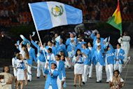 Guatemala's flagbearer Juan Ignacio Maegli (C) leads his delegation during the opening ceremony of the London 2012 Olympic Games on July 27, 2012 at the Olympic Stadium in London. AFP PHOTO / GABRIEL BOUYS
