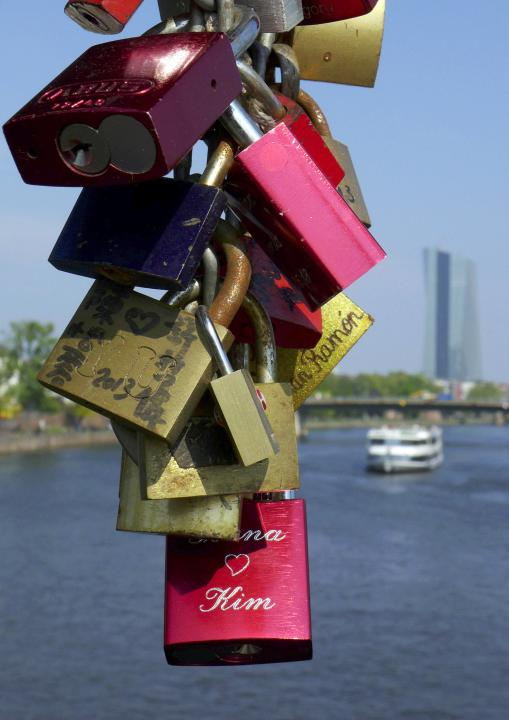 Love locks are pictured at the famous iron bridge with the new headquarters of the European Central Bank in the background at the river Main in Frankfurt