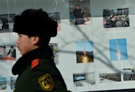 A Chinese para-military policeman marches past photos of North Korea's recent rocket launch on display outside the North Korean embassy in Beijing on February 6, 2013. US Secretary of State John Kerry warned on Thursday that North Korea's expected nuclear tests only increase the risk of conflict and would do nothing to help the country's stricken people
