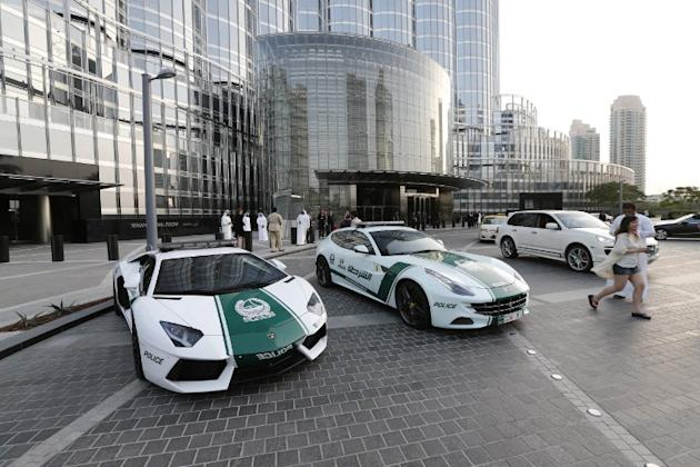 A picture taken on April 25, 2013 shows Lamborghini (L) and Ferrari police vehicles at the foot of the Burj Khalifa tower in the Gulf emirate of Dubai. Two weeks after introducing the Lamborghini poli