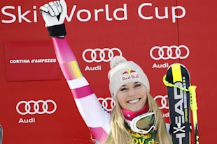 Lindsey Vonn celebrates on the podium after winning an alpine ski, women's World Cup super-G, in Cortina d'Ampezzo, Italy, Monday, Jan. 19, 2015. Lindsey Vonn won a super-G Monday for her record 63rd World Cup victory and celebrated with an embrace from a surprise visitor, boyfriend Tiger Woods. The American broke Annemarie Moser-Proell's 35-year-old record of 62 World Cup wins with a flawless run down the Olympia delle Tofane course, finishing 0.85 ahead of Anna Fenninger of Austria. (AP Photo/Andrea Solero, Ansa)