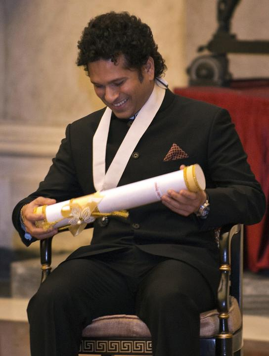 Retired cricketer Tendulkar looks at the Bharat Ratna award after receiving it from Indian President Mukherjee in New Delhi