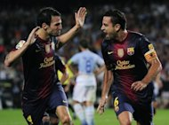 Barcelona's Xavi Hernandez (R) is congratuled by Cesc Fabregas after scoring a goal during their match against Granada on September 22. Hernandez feels their eight-point lead over Real Madrid has piled the pressure on their rivals ahead of La Liga's first clasico of the season