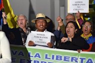 "Demonstrators hold signs reading ""We are sovereign [state], not a colony"" as they shout slogans outside the British Embassy in Quito on August 15, 2012"