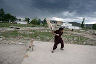 Local residents play cricket at the site of the demolished compound of slain Al-Qaeda leader Osama bin Laden in northern Abbottabad. Pakistan was in a state of high alert Wednesday over fears terrorists could mark the first anniversary of Osama bin Laden's killing by American Navy SEALs with revenge attacks