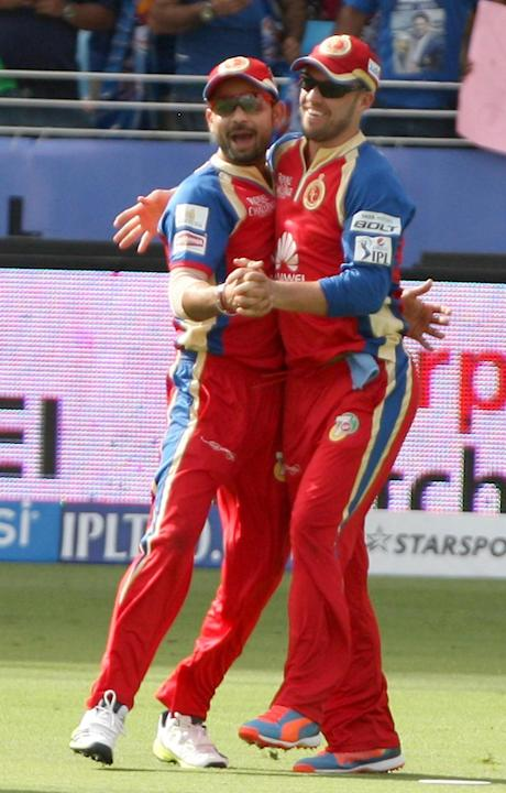 RCB players Virat Kohli and AB de Villiers celebrate fall of a wicket during the fifth match of IPL 2014 between Royal Challengers Bangalore and Mumbai Indians, played at Dubai International Cricket S