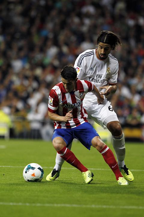 Atletico de Madrid's David Villa, left, in action with Real Madrid's Sami Khedira from Germany, right, during a Spanish La Liga soccer match at the Santiago Bernabeu stadium in Madrid, Spain, Saturday