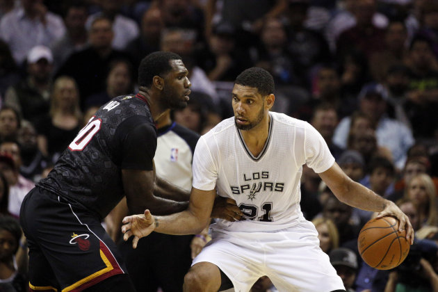 Mar 6, 2014; San Antonio, TX, USA; San Antonio Spurs forward Tim Duncan (21) is defended by Miami Heat center Greg Oden (20) during the first half at ...