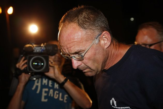 Douglas Garland is escorted into a Calgary police station late Monday, July 14, 2014. (Canadian Press)