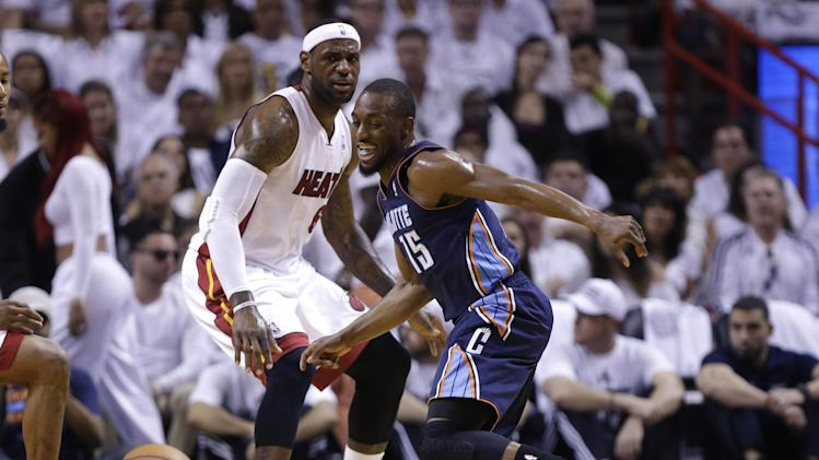 Charlotte Bobcats' Kemba Walker (15) and Miami Heat's LeBron James (6) eye a loose ball during the first half in Game 1 of an opening-round NBA basketball playoff series, Sunday, April 20, 2014, in Miami