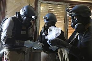 A U.N. chemical weapons expert holds a plastic bag containing samples from one of the sites of an alleged chemical weapons attack in Ain Tarma