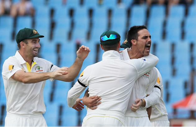 Australia's bowler Mitchell Johnson, right, with teammates reacts after dismissing South Africa's batsman Faf du Plessis, for 3 runs on the second day of their their cricket Test match at Cent