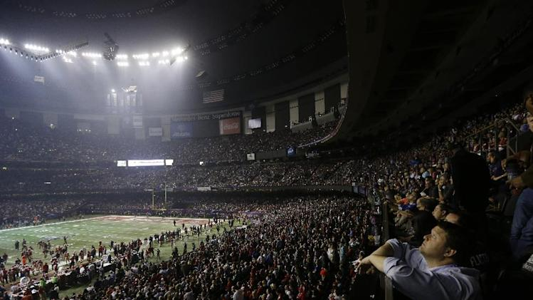 Fans and members of the Baltimore Ravens and the San Francisco 49ers wait for power to return in the Superdome during an outage in the second half of the NFL Super Bowl XLVII football game, Sunday, Feb. 3, 2013, in New Orleans. (AP Photo/Gerald Herbert)