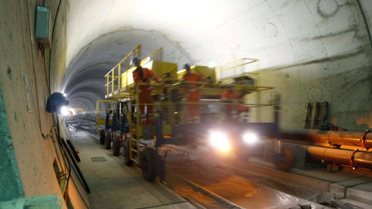 Workers drive on a special vehicle during the installation of the railway tracks in the NEAT Gotthard Base tunnel near Erstfeld