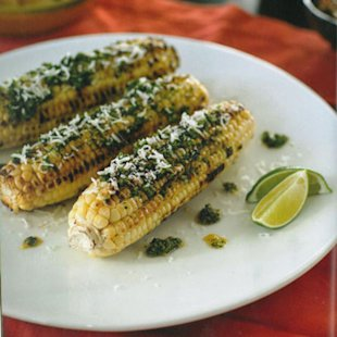 Grilled corn on the cob with pesto sauce.