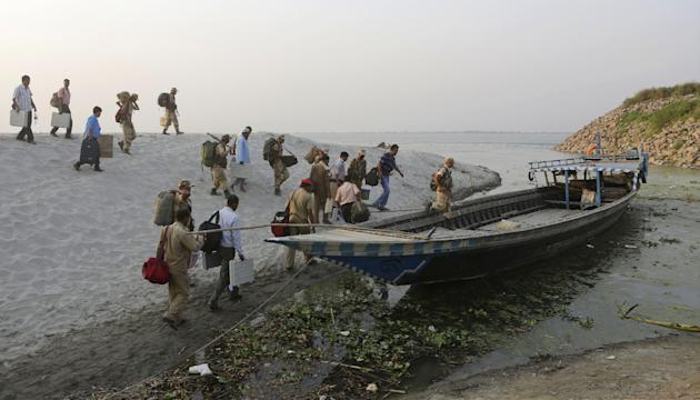 Election officers, carrying electronic voting machines, and security personnel walk towards a boat to travel to their assigned polling stations, on the eve of voting near Faturi village, about 50 kilo